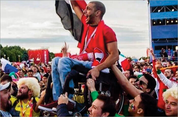 An Egyptian fan lifted by Mexican and Colombian fans at the FIFA World Cup 2018