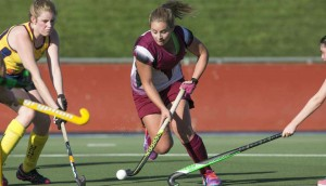 Laura Gray (maroon and white) playing for Tuggeranong Vikings Women's Hockey